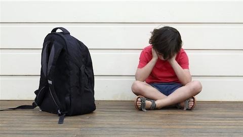 Un enfant se prenant la tête, assis avec son sac d'école.