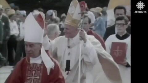 Le pape Jean-Paul II tout de blanc vêtu salue la foule lors de son voyage en Pologne.