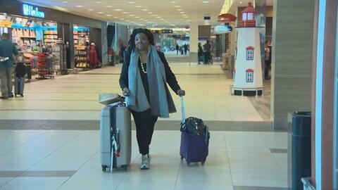 Jeanne Lehman marche dans un corridor d'aéroport, poussant ses deux valises.