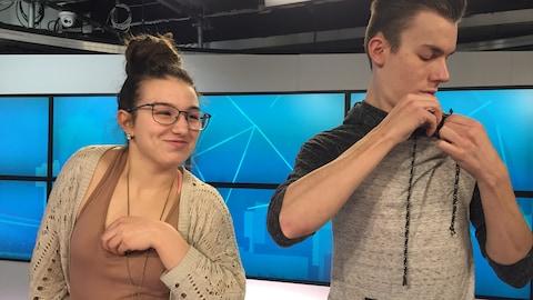 Deux élèves se trouvent sur le plateau d'une émission de télévision et placent leur micro.