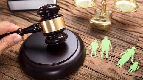 Un juge frappe son maillet près d'une représentation en papier d'une famille séparée et d'une balance.