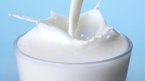 Du lait est versé dans un verre et il fait des éclaboussures. Le bon vieux lait ordinaire est tout aussi bon que le lait à valeur ajoutée.