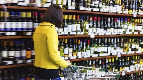 Une femme avec un chariot dans un magasin d'alcool.