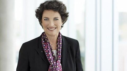 Une femme souriante porte un veston et un foulard de soie.