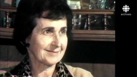 Madeleine Parent sourit.  Derrière elle se retrouve une balustrade en boiserie.