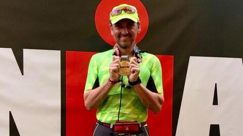 Marc Arseneau vêtu de vert avec sa médaille dorée dans les mains