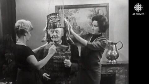 Les animatrices Nicole Germain et Ludmilla Chiriaeff aident Marius Barbeau à mettre l'habit de cérémonie du chef du clan de l'Aigle.