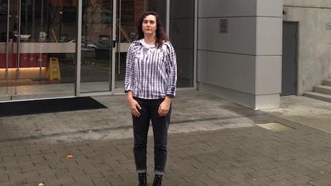 Une femme est debout devant l'édifice de Radio-Canada.