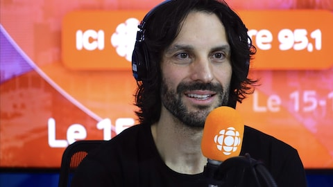 Mathieu Cyr derrière un micro dans un studio radio de Radio-Canada.