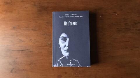 Le livre « Halfbreed » sur une table de bois ; une photo de l'autrice orne la page couverture du livre