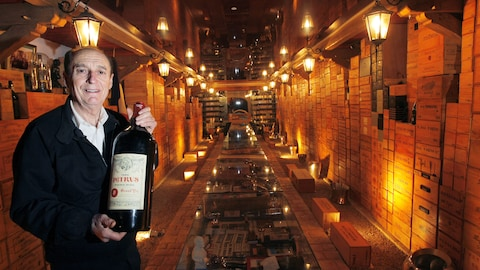 Le collectionneur de vin Michel-Jack Chasseuil pose dans sa cave avec un magnum de Château Pétrus.