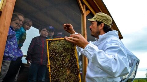 Miellerie de la Grande Ourse à St-Marc-de-Figuery (Abitibi) : on voit un apiculteur avec des abeilles et enfants