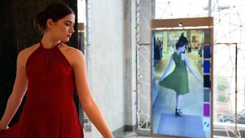 Une femme porte une robe rouge et son reflet dans le miroir porte une robe verte.