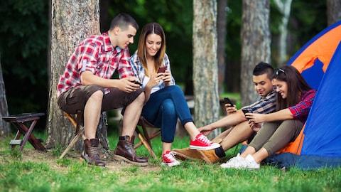 Des adeptes du camping utilisent des applications mobiles.