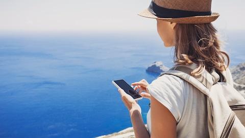 Une voyageuse consulte son téléphone intelligent devant une vue imprenable.
