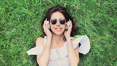Une femme couchée dans l'herbe écoute de la musique