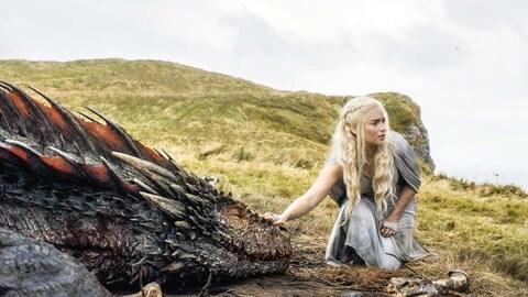L'actrice Emilia Clarke touche un dragon une scène de la série  Game of Thrones .