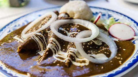 Une assiette d'enchiladas de poulet à la sauce mole.