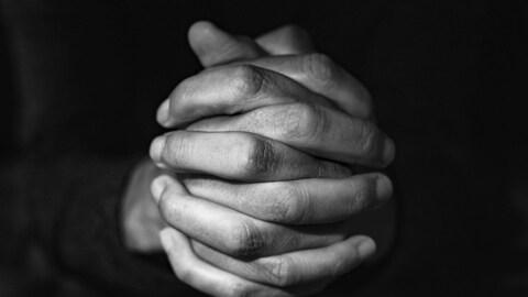 Photo en noir et blanc, en gros plan, des mains d'un homme en train de prier.