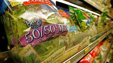 Des sacs de salade prélavée sur un présentoir d'épicerie.