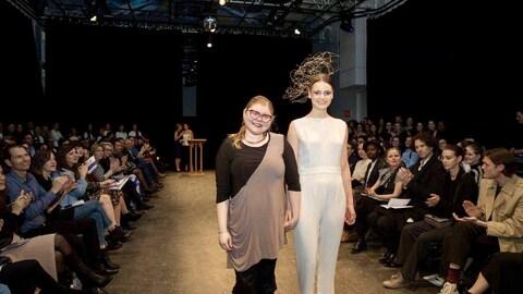 La designer accompagnée de sa mannequin sur la passerelle de mode.