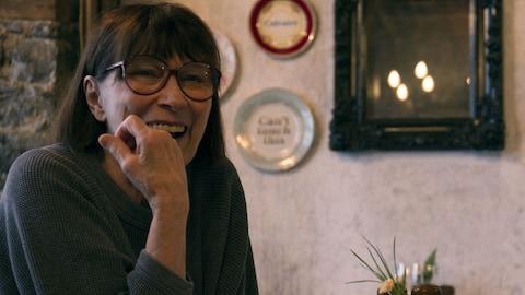 Monique Miller rie aux éclats suite à une blague de Sophie Cadieux, assises à une table d'un restaurant.