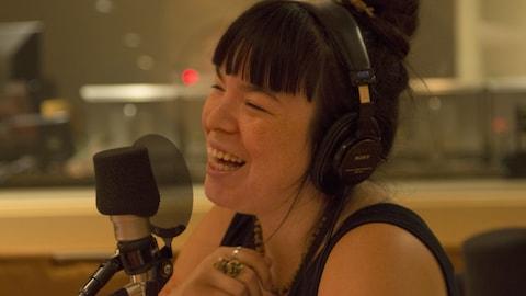Natasha Kanapé Fontaine, rie derrière un micro, est l'auteure du livre Bleuets et abricots.