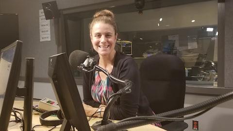 Une femme, Nathalie Nadon, devant un micro dans un studio de Radio-Canada.