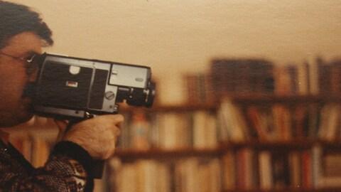 Joseph Morder filme avec une caméra Super 8 devant une bibliothèque.