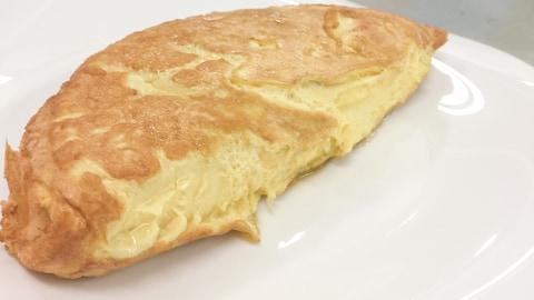L'omelette est repliée sur elle-même dans une assiette blanche.