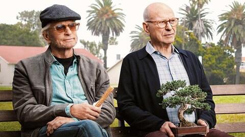 Michael Douglas et Alan Arkin sont assis sur un banc de parc, le premier avec une friandise dans les mains et le second avec un bonsaï sur les genoux.