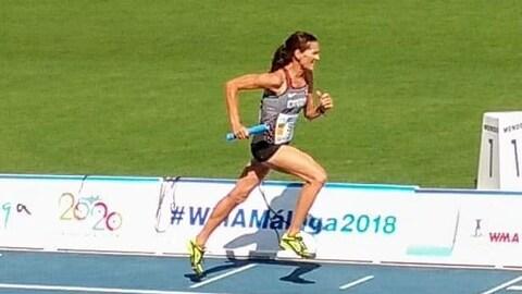 Patty Blanchard en pleine enjambée lors d'une course avec un bâton de relais à la main