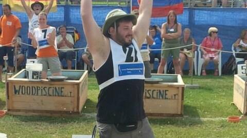 Un homme est debout dans un bac à orpaillage et lève les bras dans les airs.
