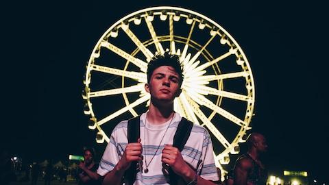 Un jeune homme qui tient les anses de son sac à dos est photographié devant une grande roue illuminée.