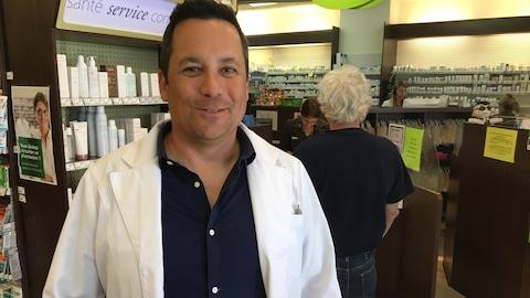 Le pharmacien-propriétaire du Proxim centre-ville Rouyn-Noranda, Sébastien Côté devant le comptoir-caisse de son commerce.