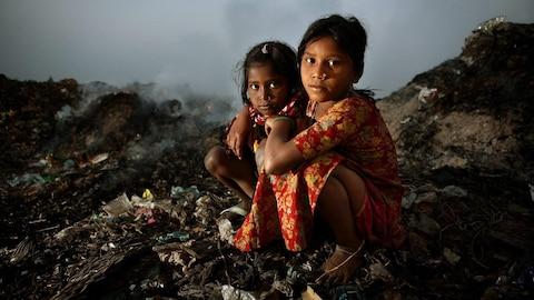 Deux jeunes filles accroupies au milieu d'un lieu désaffecté.