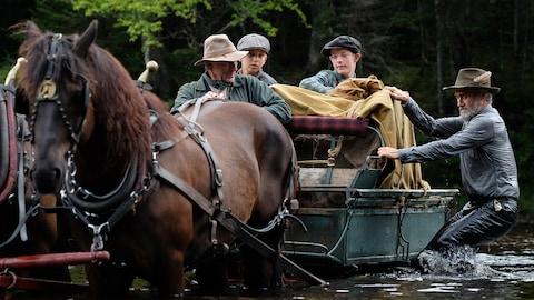 Image tirée du film Pieds nus dans l'aube mettant en vedette Roy Dupuis et Justin Leyrolles-Bouchard. Ils sont quatre, deux adultes et deux enfants dans une carriole et ils traversent une rivière.