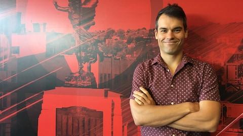 Pierre Mc Cann se tient debout sur un mur rouge sur fond de paysage et logo de Radio-Canada.