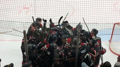 Des joueurs de hockey célèbrent un but sur la patinoire.