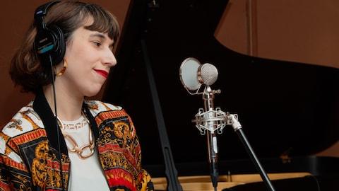 Chaîne en or, veston coloré, la chanteuse émet un sourire narquois entre deux pièces.