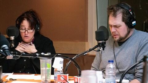 Une femme et un homme lisent un texte dans un studio de radio.