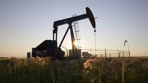 Un puits de pétrole lors d'un coucher de soleil.