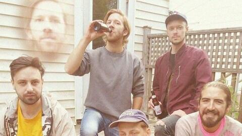 Les cinq membres du groupe, bière à la main.