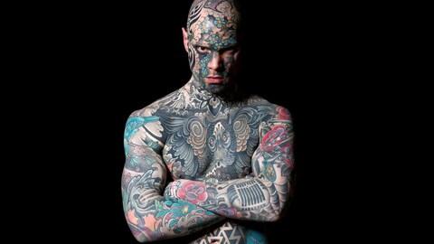 Un homme tatoué de la tête au ventre.