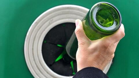 Photo d'une personne mettant une bouteille en verre dans un bac de recyclage.