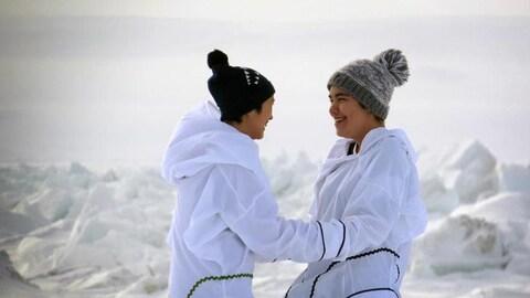 Deux jeunes chanteuses de chant de gorge éclatent de rire au terme de leur performance, devant un paysage immaculé.