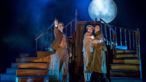 Spectacle Sherlock Holmes et le chien des Baskerville (3 comédiens sur scène, avec la lune en arrière-plan)