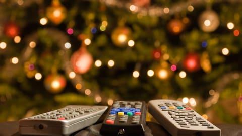 Des télécommandes devant un sapin de Noël
