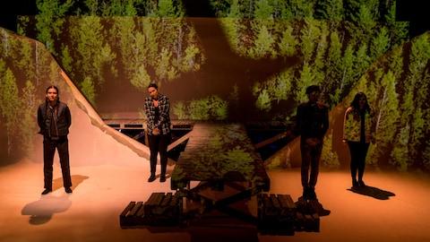 Quatre personnes se tiennent sur une scène avec un décor d'arbres.