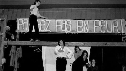 Quatre acteurs de théâtre sont sur scène, l'un d'entre eux marche sur une poutre surélevée.